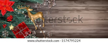 Merry Christmas and Happy New Year decorative banner with a gift, fir tree branches, golden deer figurine, poinsettia flowers and sparkling transparent glass snowflakes. Horizontal Christmas poster #1574795224