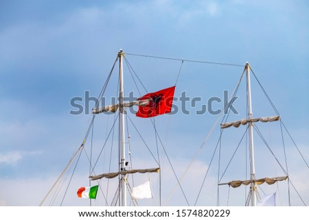 Mast of vintage mast wooden sailing ship for sea tours in port of Saranda, Albania with red state albanian flag with black double-headed eagle, and italian flag. #1574820229