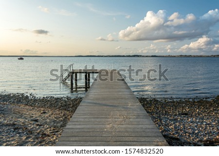 Wooden pier at the calm Baltic Sea in scenic evening light #1574832520