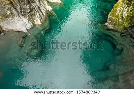 Makaroa Blue Pool located in Mount Aspiring National park in South Island, New Zealand.Crystal clear mountain river. Royalty-Free Stock Photo #1574889349