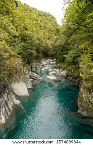 Makaroa Blue Pool located in Mount Aspiring National park in South Island, New Zealand.Crystal clear mountain river. Royalty-Free Stock Photo #1574889844