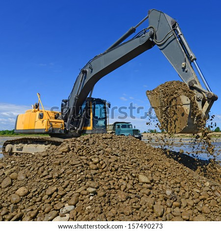 Extracting and loading gravel excavated in the mainstream of the river #157490273