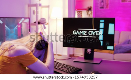 Blonde girl upset she lost on a shooter online game. Game over for player girl. Girl sitting on gaming chair. #1574933257
