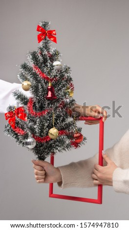 The hands of two girls hold a red frame through which one girl holds out a decorated xmass tree, a symbol of the New Year and Christmas. Greeting card. Symbolism, abstraction and minimalism concept. #1574947810