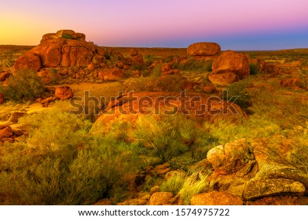 Aerial view of amazing natural landscapes whit light sun and their deep red color of Devils Marbles. These gigantic boulders have become a symbol of Australia's outback, Northern Territory, Australia. Royalty-Free Stock Photo #1574975722