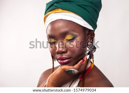 Studio portrait of African young woman with vibrant makeup of yellow and green colors. Colorful ethnic headwrap. White background. Fashion style.