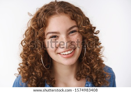 Close-up carefree smiling young female student curly-haired freckles acne prone skin smiling broadly friendly-looking camera hanging out friends playfully giggling, standing white background Royalty-Free Stock Photo #1574983408