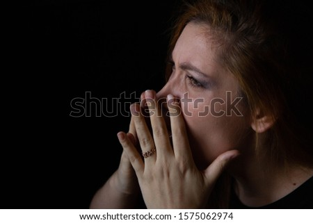 portrait of a young beautiful woman who blows her nose on a black background. #1575062974