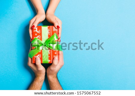 Top view of two people sharing a present on colorful background. Holiday and surprise concept. Close up. #1575067552