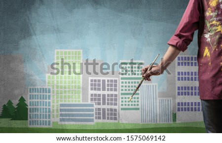 Close up artist hand holding paintbrush. Painter in shirt standing on background colorful picture of city. Modern cityscape with high skyscrapers artwork. Creative hobby and artistic occupation. #1575069142