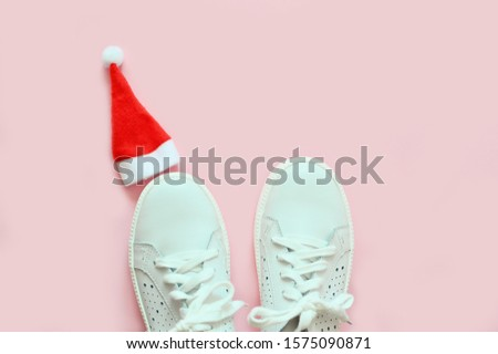 White sneakers and Santa Claus hat on a pink pastel background. The concept of the New Year, Christmas. Fitness concept. Copy space. Top view. flat lay. Fashion blog or magazine concept. #1575090871
