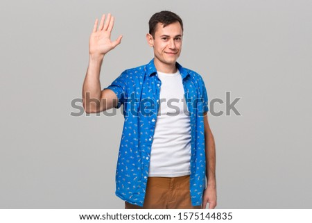 Positive man waving hand to say hello isolated over grey background. Saying hi #1575144835