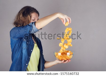 Portrait of a cute young girl throwing chips in glass bowl full of chips.
