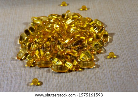 Yellow gelatin capsules with omega 3 and omega 6 polyunsaturated fatty acids close-up #1575161593