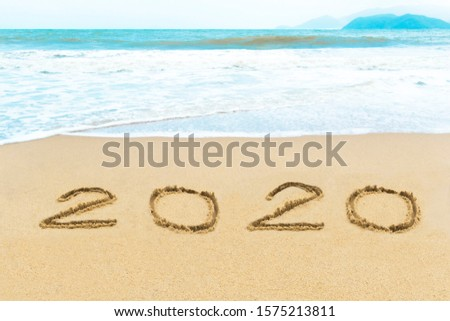 Happy 2020 new year concept. Letters, numbers inscription written, handwritten on the wet golden sand on the background of sea shore. Text on the beach, vacation on winter holidays. Sunny hot weather. #1575213811