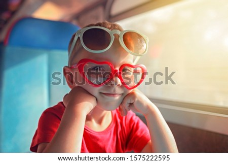 Cute little boy wearing some sun glasses in a pile and travelling by train during vacation, transport, family vacation and summertime, lifestyle inside portrait Royalty-Free Stock Photo #1575222595
