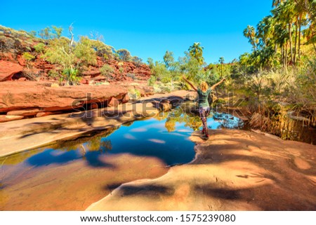 Carefree woman enjoying sandstone cliffs and red Cabbage Palm reflecting on waterhole in Palm Valley Oasis, Finke Gorge National Park. Tourism Outback Safari in Northern Territory, Central Australia. Royalty-Free Stock Photo #1575239080