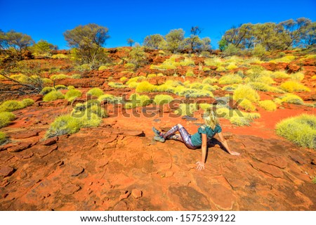 Tourist woman relaxing during the hiking along Arankaia Walk with bush vegetation and red desert sand in Palm Valley, Finke Gorge National Park. Tourism in Australia Outback, Northern Territory. Royalty-Free Stock Photo #1575239122