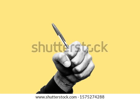 Concept of freedom of speech and information, stop censorship. Hand holding a pen like a weapon. Defend the freedom of Journalism. Black and white subject with a yellow background #1575274288