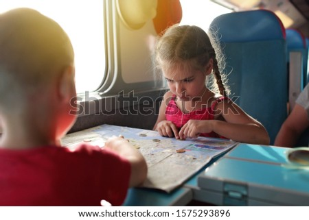 Cute little boy discussing with his smiling sister their economy vacations during travelling time by train, transport, happy family vacation and summertime, lifestyle inside portrait #1575293896