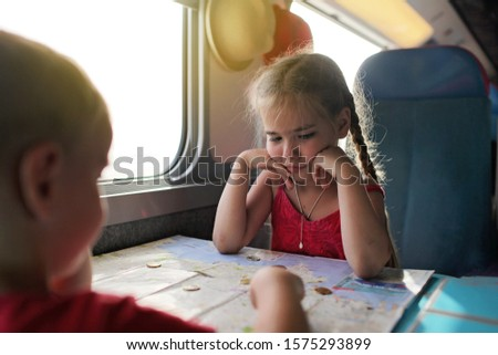 Cute little boy discussing with his smiling sister their economy vacations during travelling time by train, transport, happy family vacation and summertime, lifestyle inside portrait #1575293899