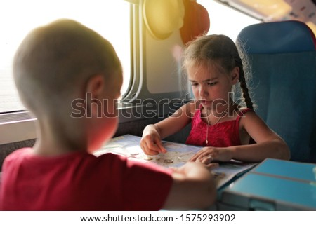 Cute little boy discussing with his smiling sister their economy vacations during travelling time by train, transport, happy family vacation and summertime, lifestyle inside portrait #1575293902