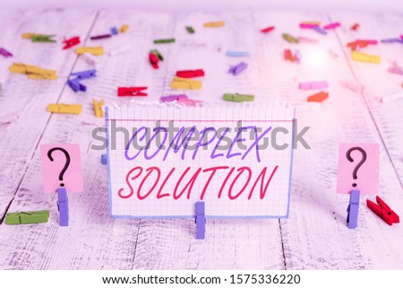 Conceptual hand writing showing Complex Solution. Business photo showcasing significant ideas that are completely or partly repressed Crumbling sheet with paper clips placed on the wooden table. #1575336220