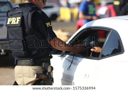 SALVADOR, BAHIA / BRAZIL - October 11, 2018: Federal Highway Police (PRF) officer approaches the driver on the BR 324 federal highway in Salvador (BA). #1575336994
