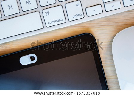 A White Color Camera Privacy Cover. Slide Webcam. Cover for an electronic device with a keyboard on a wooden table Royalty-Free Stock Photo #1575337018