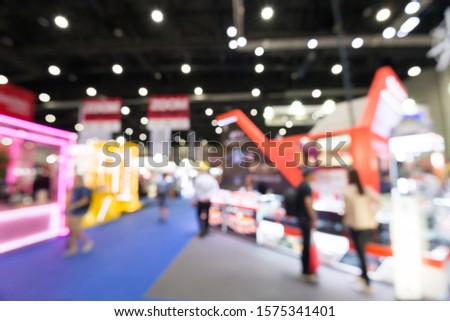 Abstract blur people in exhibition hall event trade show expo background. Large international exhibition, convention center, MICE business industry concept #1575341401