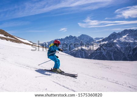 Little boy in blue and yellow ski costume skiing in downhill slope. Winter sport recreational activity #1575360820
