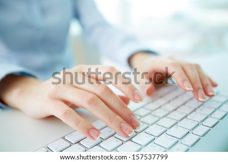 Female office worker typing on the keyboard Royalty-Free Stock Photo #157537799