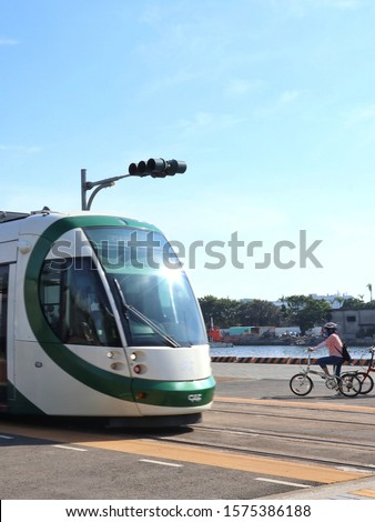 Kaohsiung / Taiwan - Nov 21, 2019 A cyclist was riding a bike while a light rail train passed by. #1575386188