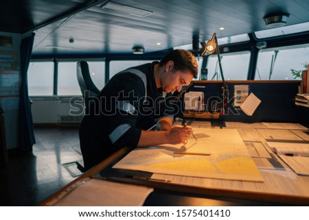 Marine navigational officer during navigational watch on Bridge . He does chart correction of nautical maps and publications. Work at sea #1575401410