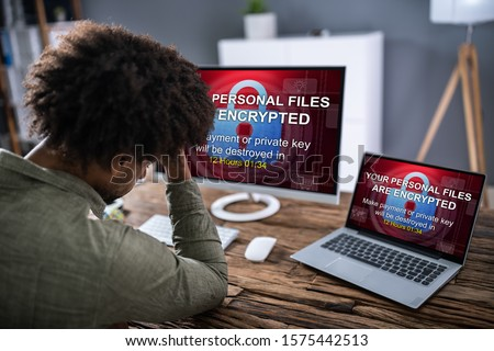 Close-up Of Worried Businessman Encrypted Text On The Laptop Over The Wooden Desk #1575442513