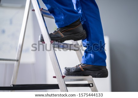 Low Section View Of A Handyman's Foot Climbing Ladder #1575444133