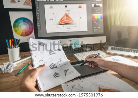 Graphic designer drawing sketches logo design. The concept of a new brand. Professional creative occupation with idea. Royalty-Free Stock Photo #1575501976