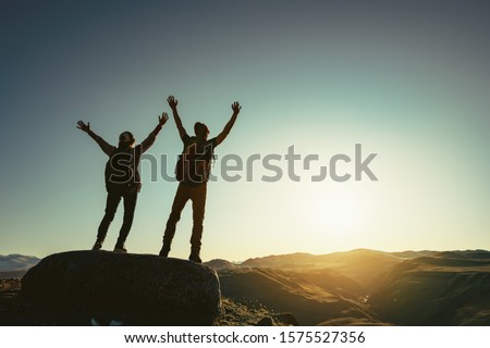 Two happy hikers stands with raised arms against sunset and enjoys mountains view #1575527356
