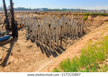 Pile driving in foundation pit construction apartment building. Piling driven ground. Deep foundation installation. Reinforce prestressed concrete piles factory foundation construction  #1575533887