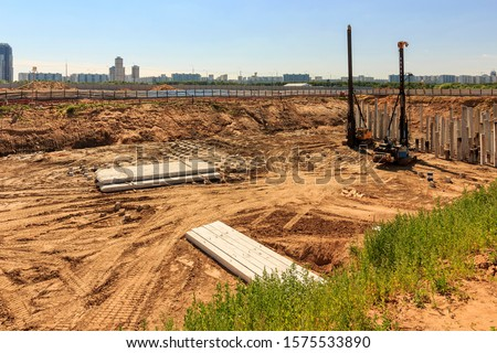 Pile driving in foundation pit construction apartment building. Piling driven ground. Deep foundation installation. Reinforce prestressed concrete piles factory foundation construction  #1575533890