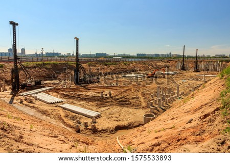 Pile driving in foundation pit construction apartment building. Piling driven ground. Deep foundation installation. Reinforce prestressed concrete piles factory foundation construction  #1575533893