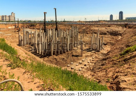 Pile driving in foundation pit construction apartment building. Piling driven ground. Deep foundation installation. Reinforce prestressed concrete piles factory foundation construction  #1575533899