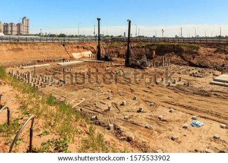 Pile driving in foundation pit construction apartment building. Piling driven ground. Deep foundation installation. Reinforce prestressed concrete piles factory foundation construction  #1575533902