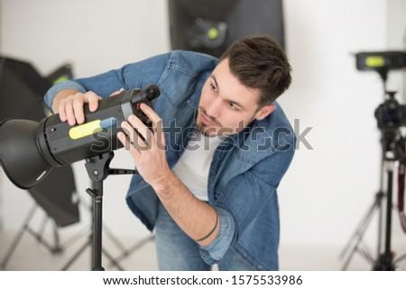 a man fixing the lighting equipment #1575533986