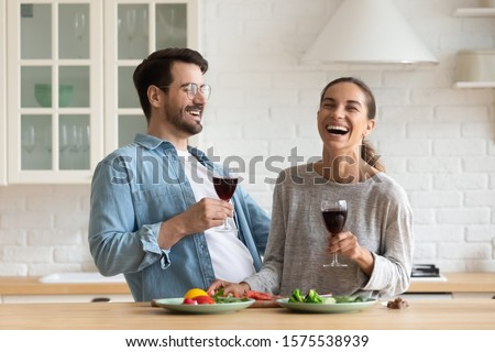 Happy young romantic couple cooking drinking red wine in modern kitchen, cheerful affectionate millennial boyfriend and girlfriend holding glasses enjoying laughing preparing healthy salad at home