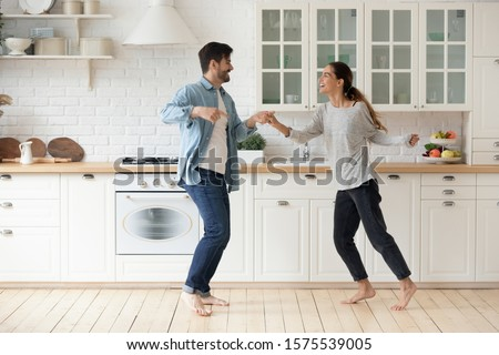 Happy couple having fun dancing together in modern kitchen enjoying lifestyle, active funky young husband and wife first time home buyers moving listening music laughing celebrating freedom party #1575539005