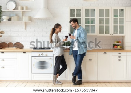 Romantic affectionate beautiful young couple holding glasses standing in modern cozy white kitchen room interior, happy married guy husband and girl wife drinking red wine celebrate together at home