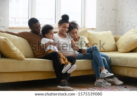 Happy young biracial parents relax on comfortable couch with little kids have fun watch video on smartphone together, african American family rest on sofa in living room using cellphone with children #1575539080