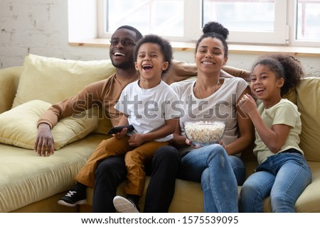 Overjoyed young african American parents relax with preschooler kids on weekend at home watching funny video together, happy biracial family with children have fun enjoy movie time in living room