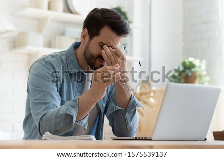 Tired young man feel pain eyestrain holding glasses rubbing dry irritated eyes fatigued from computer work, stressed man suffer from headache bad vision sight problem sit at home table using laptop Royalty-Free Stock Photo #1575539137